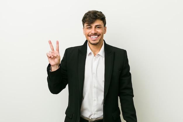 Młody biznesowy mężczyzna pokazuje zwycięstwo znaka i ono uśmiecha się szeroko