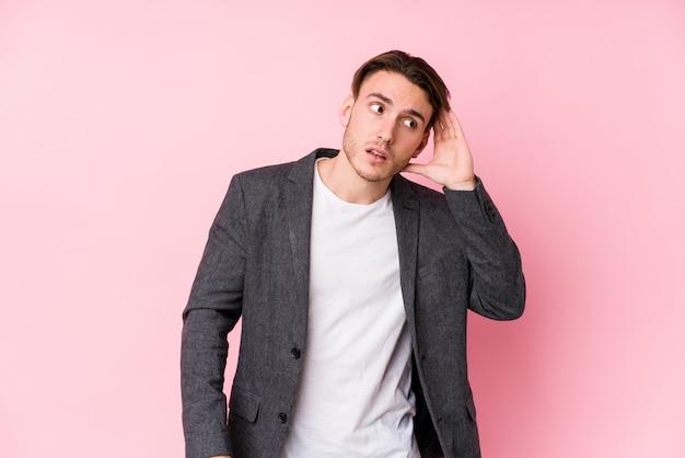 Młody biznesowy mężczyzna pozuje próbować słuchać plotki