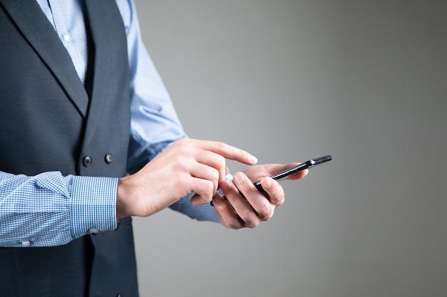 Młody biznesowy mężczyzna trzyma inteligentny telefon.