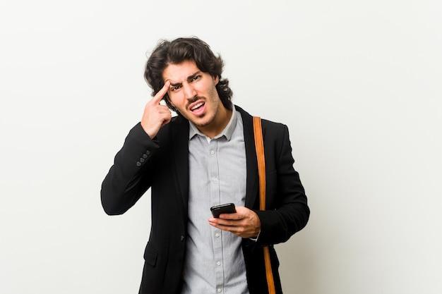 Młody biznesowy mężczyzna trzyma telefon pokazuje rozczarowanie gest z palcem wskazującym.