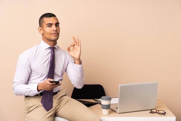 Młody biznesowy mężczyzna w biurze pokazuje ok znaka z palcami