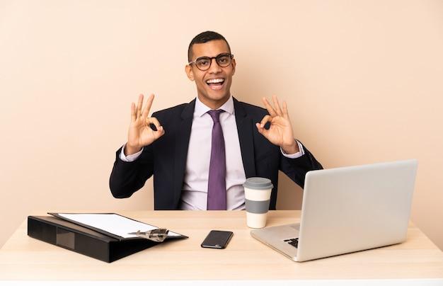 Młody biznesowy mężczyzna w jego biurze z laptopem i innymi dokumentami pokazuje ok znaka z palcami