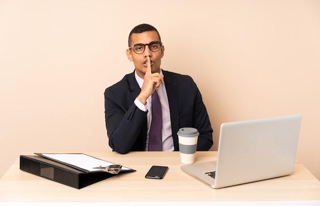 Młody biznesowy mężczyzna w jego biurze z laptopem i innymi dokumentami pokazuje znaka cisza gesta kładzenia palec w usta