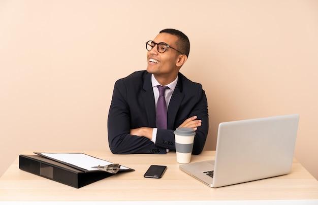 Młody biznesowy mężczyzna w jego biurze z laptopem i innymi dokumentami szczęśliwymi i uśmiechniętymi