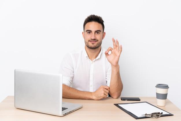 Młody biznesowy mężczyzna z telefonem komórkowym w miejscu pracy pokazuje ok znaka z palcami