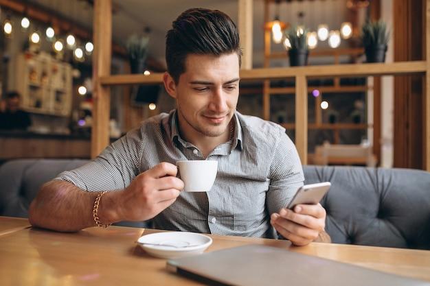 Młody biznesowy mężczyzna z telefonem w kawiarni