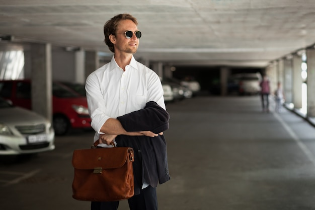 Młody biznesowy pracownik w okularach przeciwsłonecznych stoi na parking