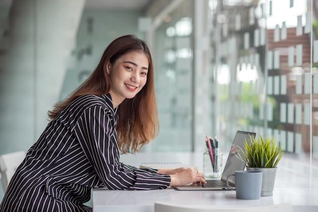 Młody bizneswoman azjatyckiego pracuje nad siedzeniem przy stole w biurze