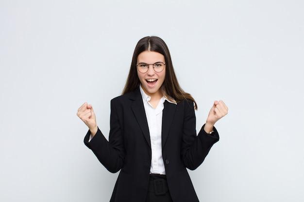 Młody bizneswoman czuje się szczęśliwy, zaskoczony i dumny, krzycząc i świętując sukces z wielkim uśmiechem na białej ścianie