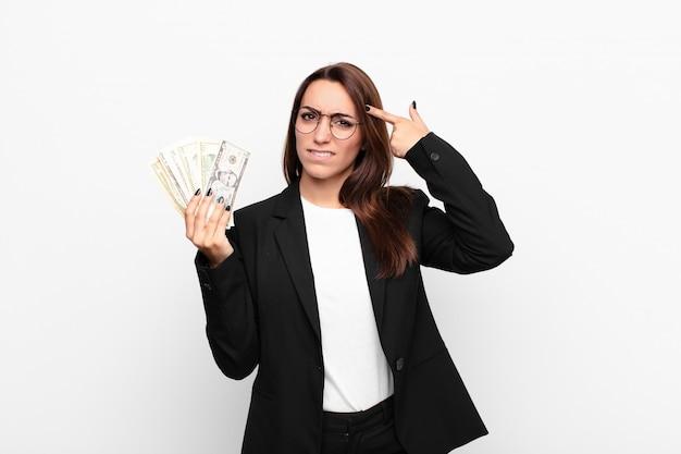 Młody bizneswoman czuje się zmieszany i zdziwiony, pokazując, że jesteś szalony
