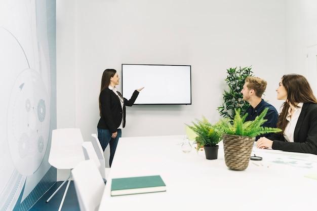 Młody bizneswoman daje prezentaci w biurze