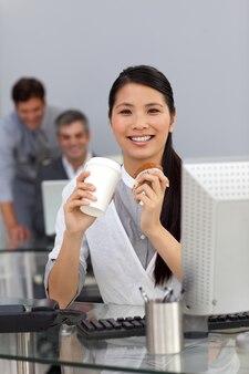 Młody bizneswoman je słodka bułeczka i pije kawę