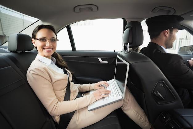 Młody bizneswoman jest chauffeured podczas gdy pracujący