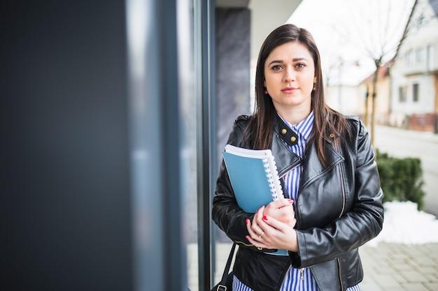 Młody bizneswoman jest ubranym czarną kurtki mienia książki