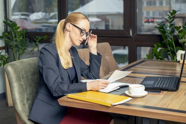 Młody bizneswoman jest ubranym szkła siedzi przy miejscem pracy i czyta papiery przy biurem.