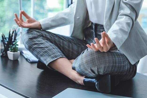 Młody bizneswoman medytuje w biurze