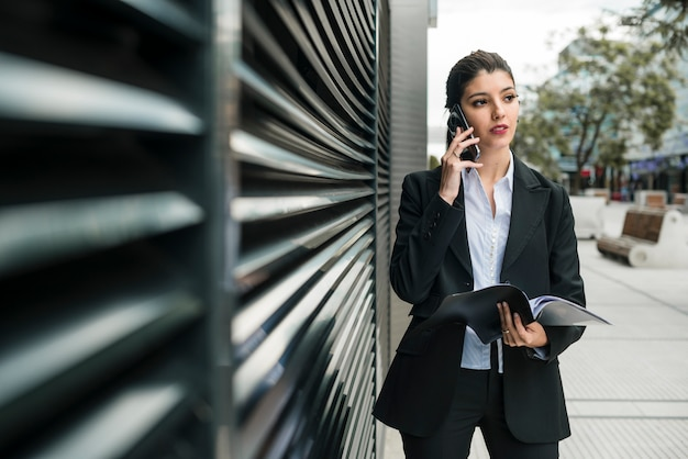 Młody bizneswoman opowiada na telefonu komórkowego mienia falcówce w ręce patrzeje daleko od