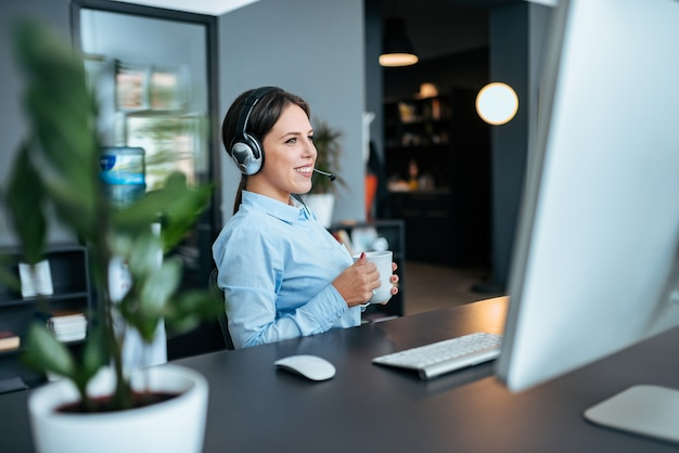 Młody bizneswoman opowiada z klientem nad słuchawki.
