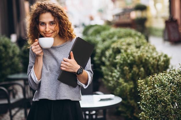 Młody bizneswoman pije kawę na zewnątrz cukiernianego mienie laptopu