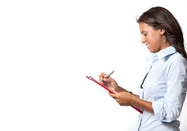 Młody bizneswoman pisze w arkuszu
