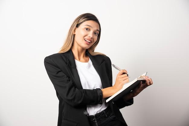 Młody bizneswoman pisze w schowku ołówkiem.