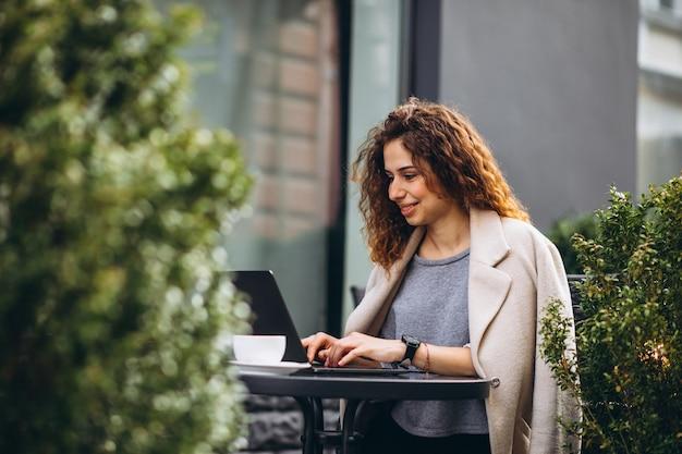 Młody bizneswoman pracuje na komputerze na zewnątrz kawiarni