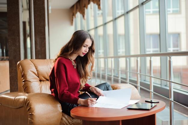 Młody bizneswoman pracuje na laptopie podczas gdy czekający na jej flig