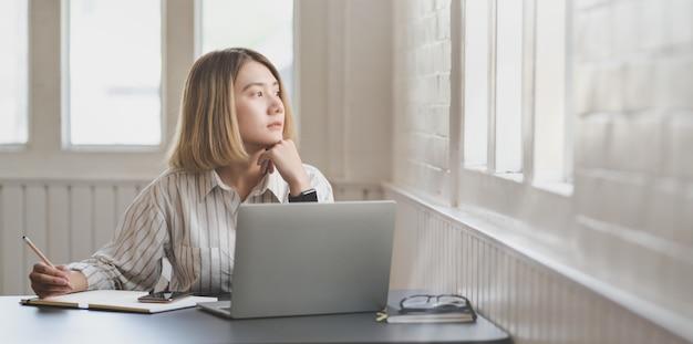 Młody bizneswoman pracuje nad jej projektem i pisze na notatniku