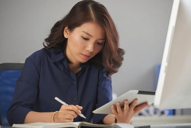 Młody bizneswoman robić notatkom