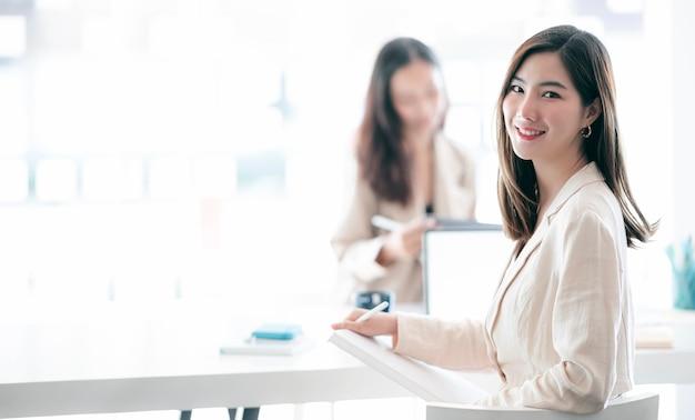 Młody bizneswoman siedzi przy biurku i pracuje. uśmiechając się i patrząc na kamerę.