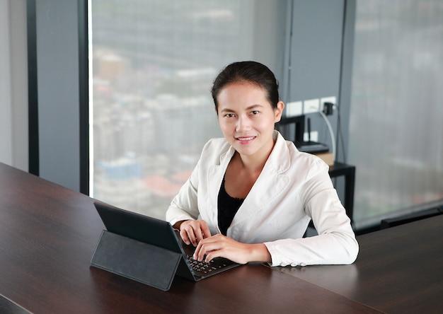 Młody bizneswoman siedzi przy stołem na miejscu pracy w biurze z laptopem