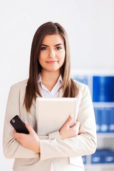 Młody bizneswoman trzyma cyfrową pastylkę i telefon komórkowy