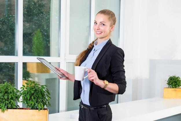 Młody bizneswoman trzyma pastylkę z listą zadań i pije jej ranek kawę w nowożytnym jaskrawym biurze