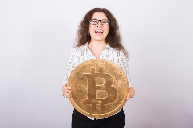 Młody bizneswoman trzyma złotego bitcoina