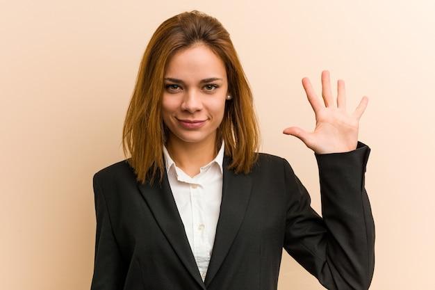 Młody bizneswoman uśmiecha się rozochoconego seans liczba pięć z palcami