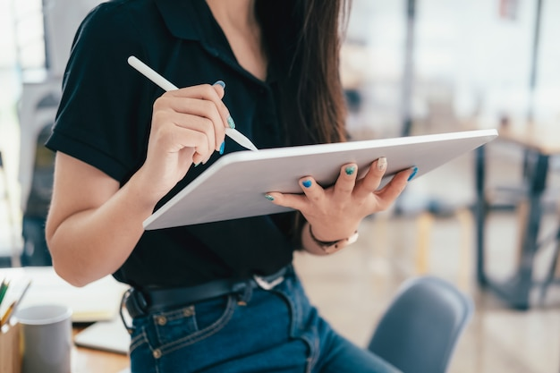 Młody bizneswoman używa pastylki gmerania informację wprowadzać na rynek online.