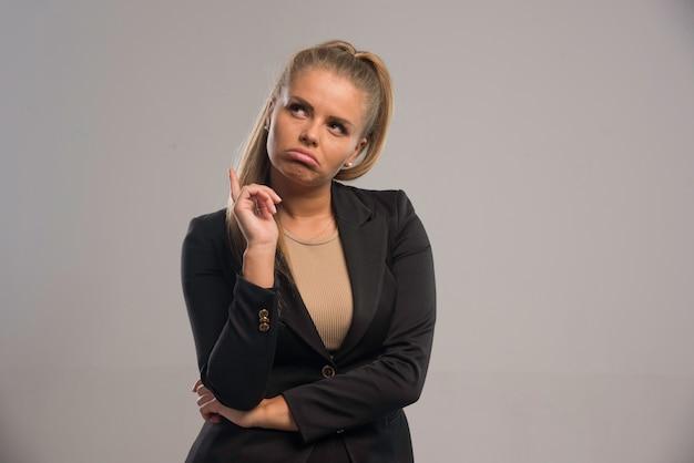 Młody bizneswoman w czarnym garniturze myślenia.