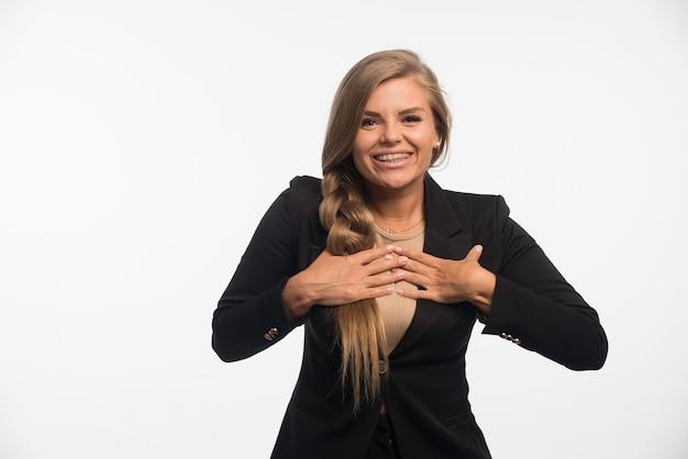Młody bizneswoman w czarnym garniturze wygląda na szczęśliwego.