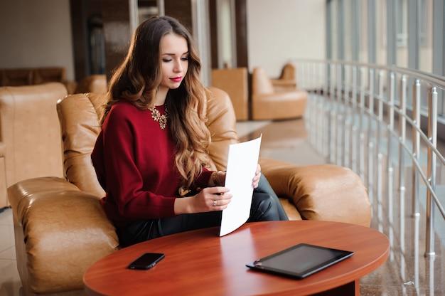 Młody bizneswoman w czerwonym pulowerze pracuje z papierami