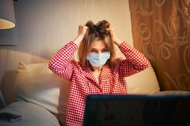Młody bizneswoman w medycznej masce ochronnej pracuje z domu przy komputerze podczas samoizolacji i kwarantanny. v.