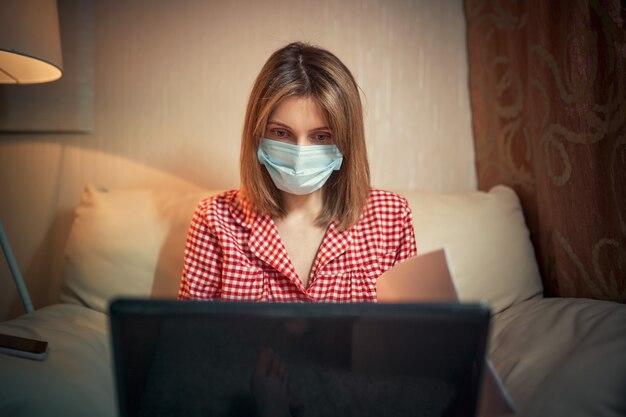 Młody bizneswoman w medycznej masce ochronnej pracuje z domu przy komputerze podczas samoizolacji i kwarantanny. wybuch koronawirusa wirusa, epidemia grypy i powieść covida ncova. zostań w domu.