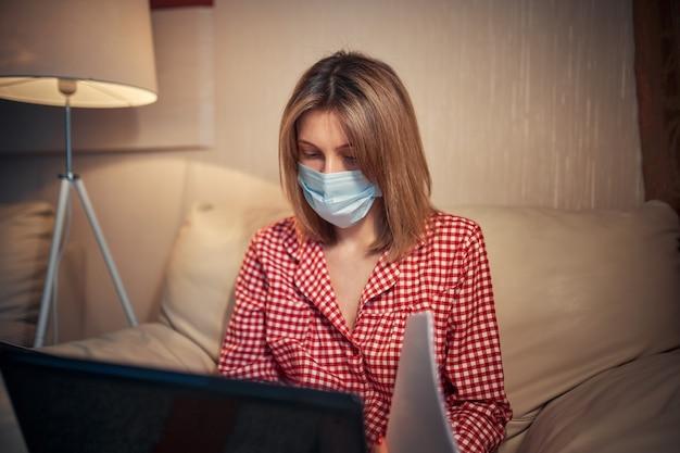 Młody bizneswoman w medycznej masce ochronnej pracuje z domu przy komputerze podczas samoizolacji i kwarantanny.