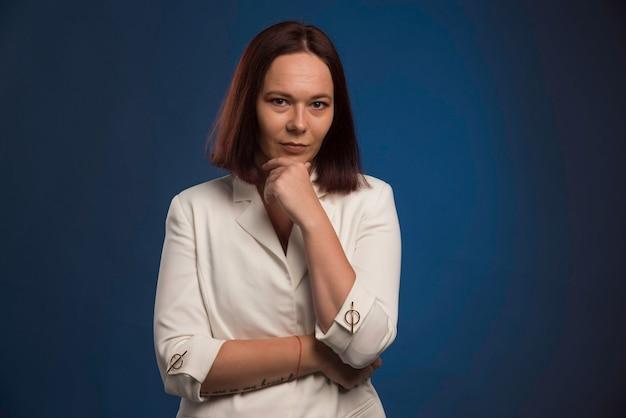 Młody bizneswoman w myśleniu biały blezer.