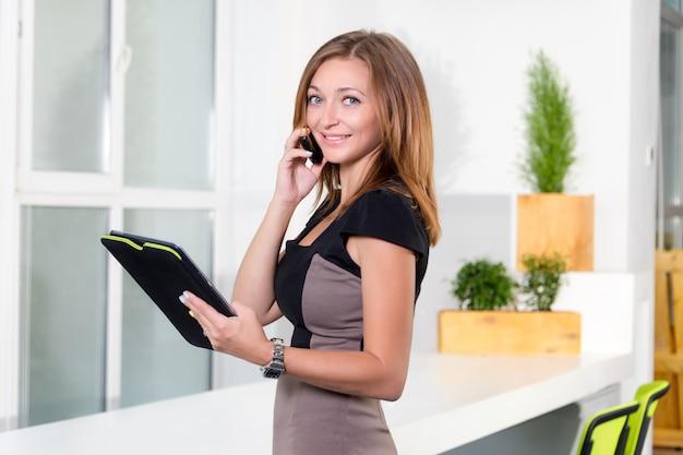 Młody bizneswoman w nowożytnym jaskrawym biurze opowiada na telefonie komórkowym i trzyma pastylkę z listą zadania