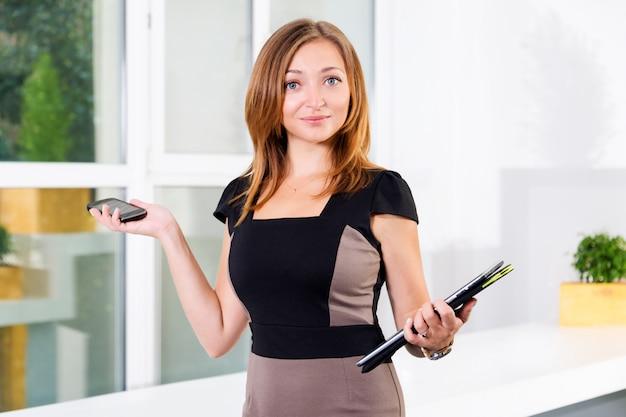 Młody bizneswoman w nowożytnym jaskrawym biurze trzyma smartphone i pastylkę z listą zadania