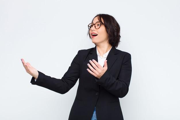 Młody bizneswoman wykonuje operę lub śpiewa na koncercie lub przedstawieniu, czując się romantyczny, artystyczny i namiętny na białej ścianie