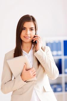Młody bizneswoman z cyfrową pastylką i telefonem komórkowym