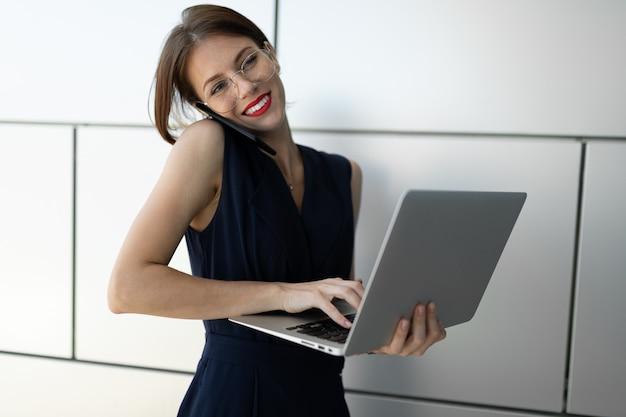 Młody bizneswoman z laptopem w jej rękach opowiada na telefonie. biznesowy portret na szarym ściennym tle, spojrzenie przy kamerą