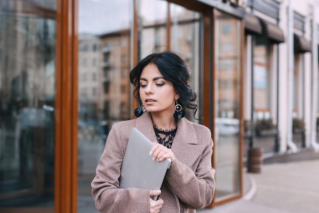 Młody bizneswoman z laptopu odprowadzeniem na miasto ulicie outdoors