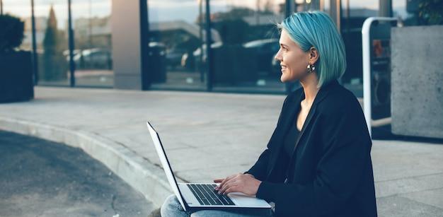 Młody bizneswoman z niebieskimi włosami siedzi na ulicy i pracuje na laptopie